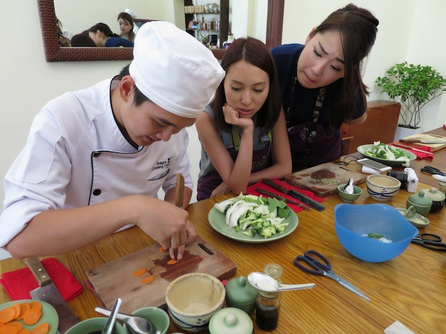 Chef Khang showing the girls how to carve a carrot butterfly.