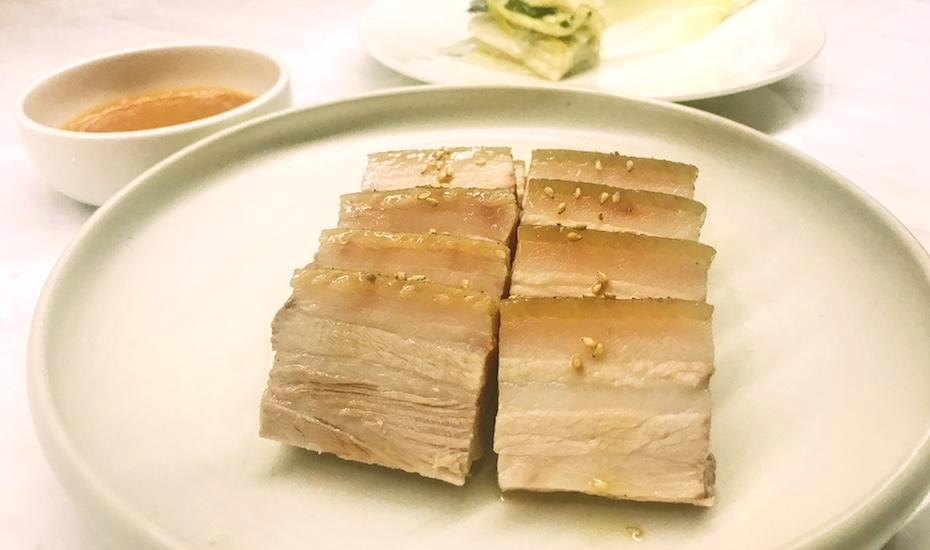 Kimme's take on traditional bossam: that pork belly is cooked for 12 hours. Wrap it in the endive leaves with white kimchi and chilli paste.