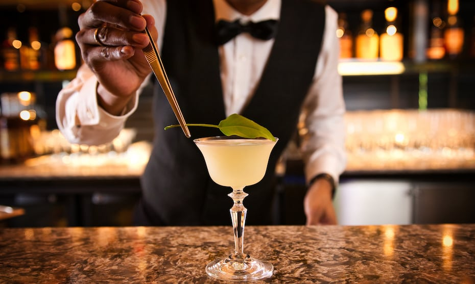 A bartender presents a cocktail at The NCO Club's Madame Fan