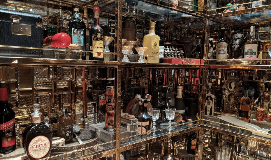 Idlewild's cabinet of curiostiy holds rare spirits, antiques found along the transatlantic route, old paper clippings and luggage tags even.