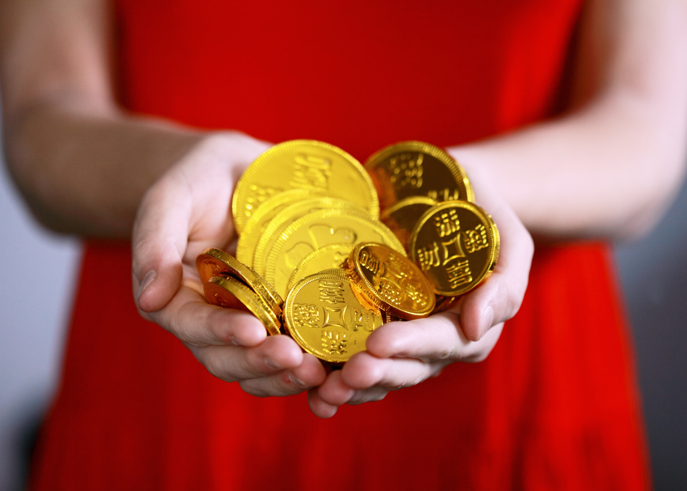 woman in red holding chocolate gold coins