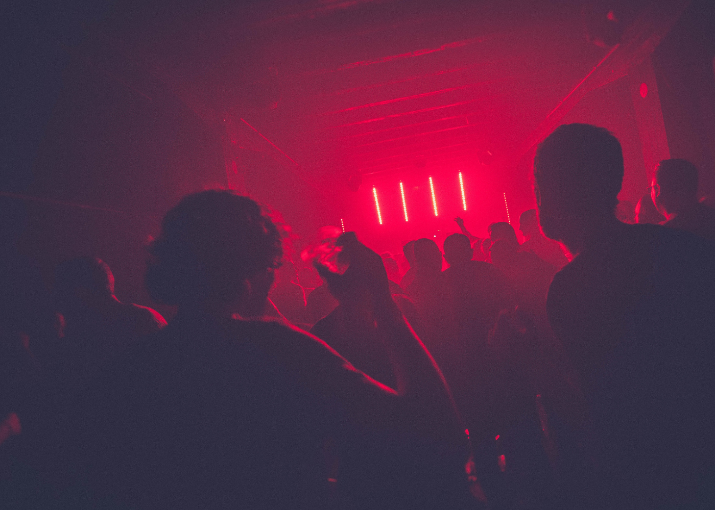 An image of people dancing in a club under red light