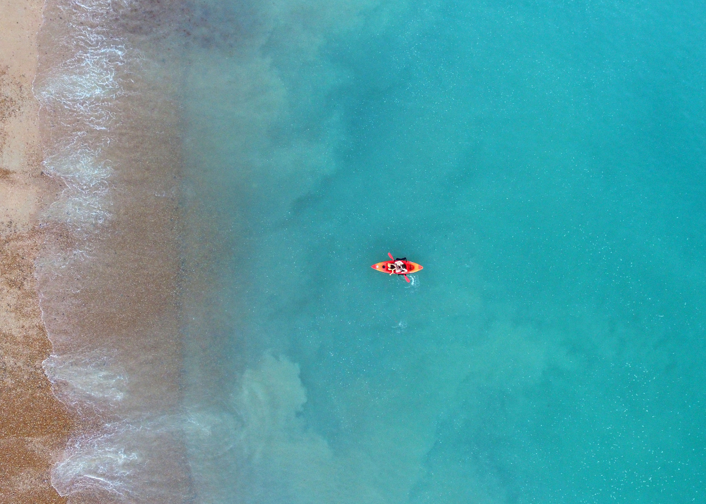 A person rowing a kayak in the sea towards the beach