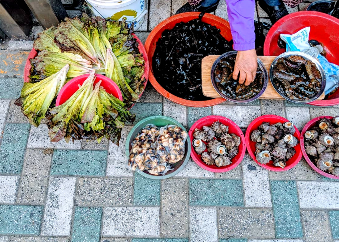 A local granny selling sea cucumbers and shellfish by the street.