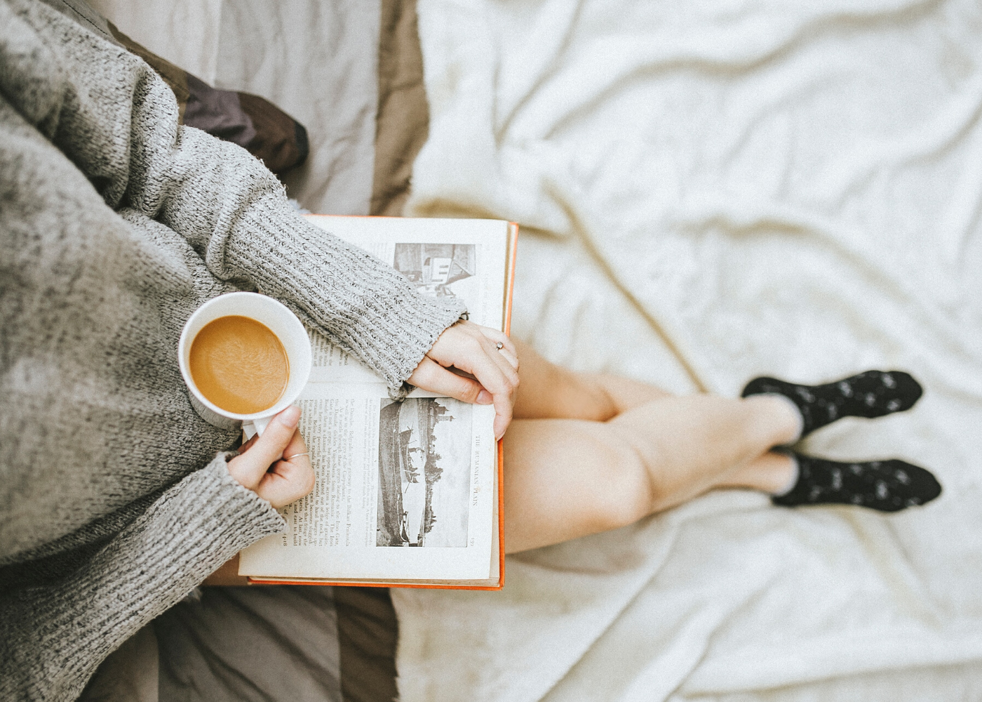 woman holding coffee and book