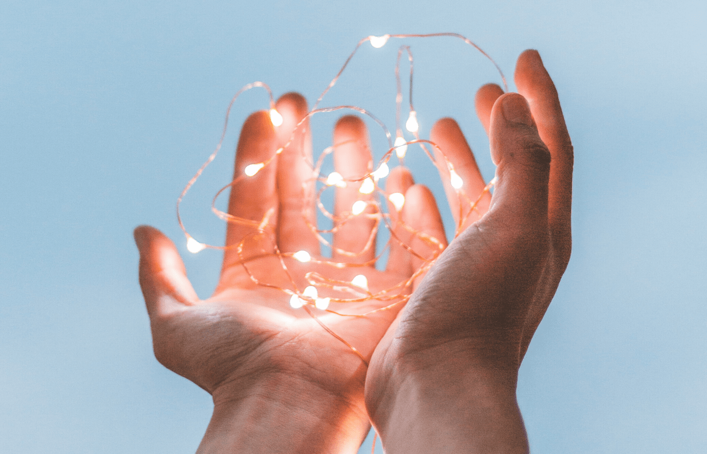 hands holding fairy lights | how to help covid-19