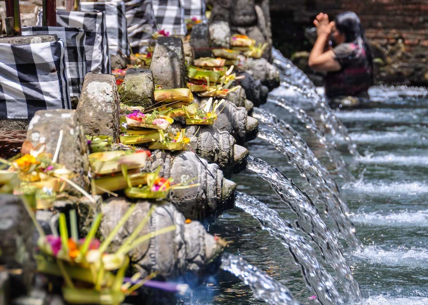 Woman batheing at Pura Tirta Empul - one of the most sacred water temples in Bali, Indonesia