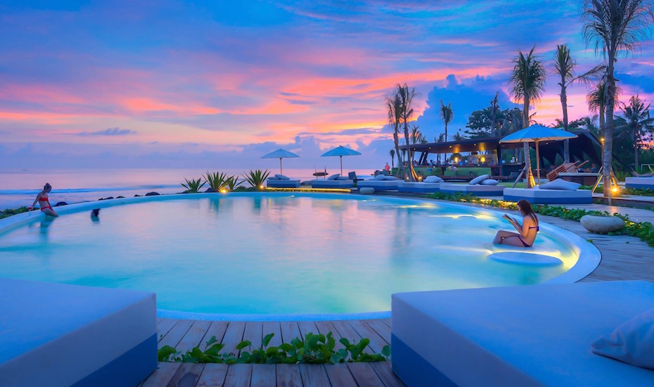 Glowing beachfront infinity pool at sunset at Komune Beach Club in Keramas, Bali - Indonesia