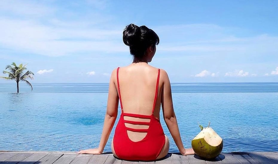 Girl and coconut at the beachfront infinity pool at Alila Seminyak in Bali - Indonesia