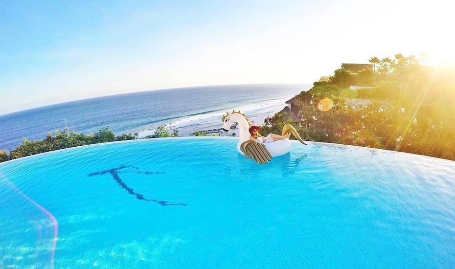 Girl on floatie in the clifftop infinity pool at Karma Kandara resort in Uluwatu, Bali - Indonesia