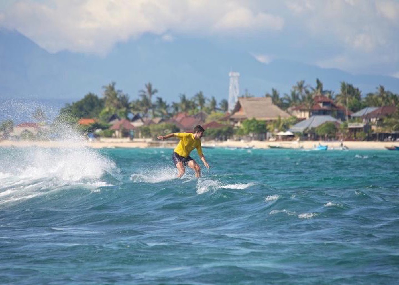 Surfer riding the waves in Nusa Lembongan, Bali, Indonesia