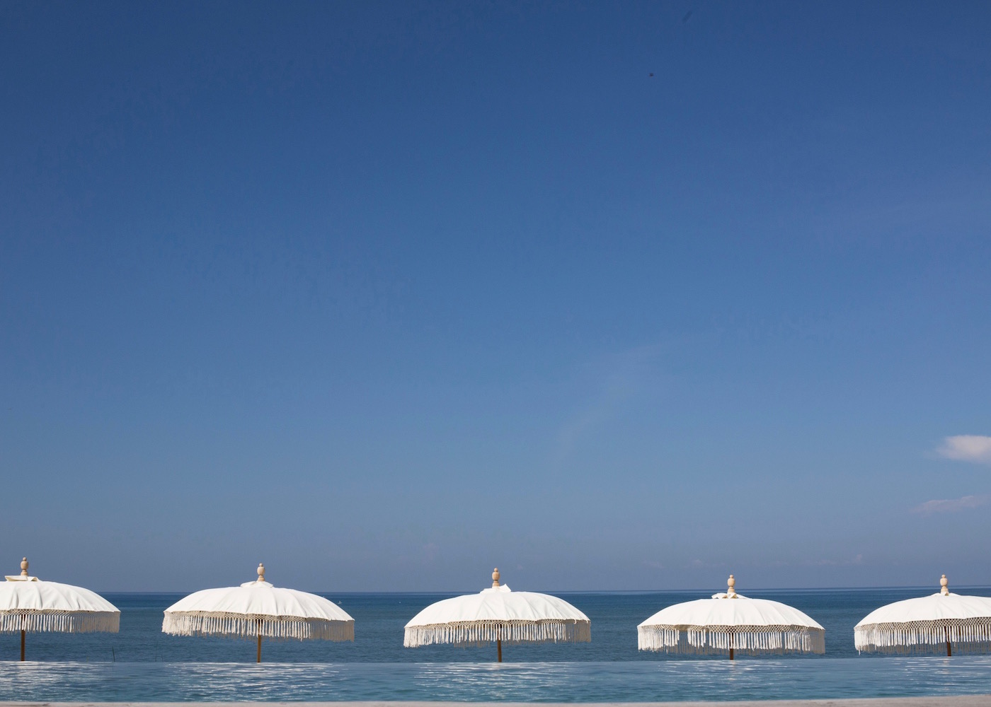 White umbrellas and infinity pool overlooking the ocean at The Lawn beach club in Canggu, Bali, Indonesia