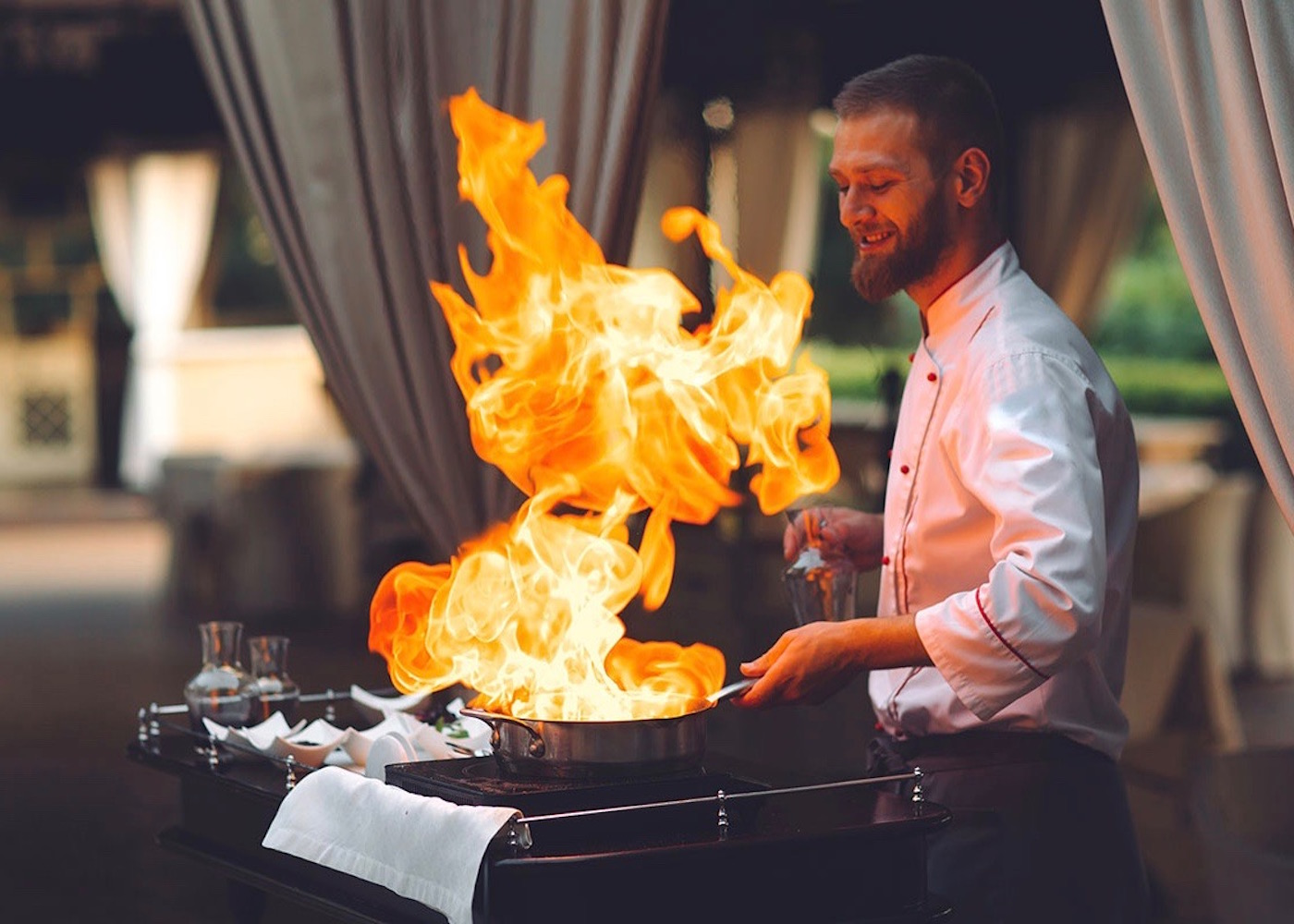 Chef cooking with fire at KAZA Restaurant at Kanvaz Village Hotel & Resort in Seminyak, Bali - Indonesia