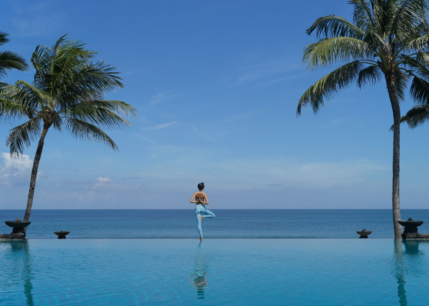A woman doing yoga at Wellness by The Legian's infinity swimming pool facing Seminyak beach