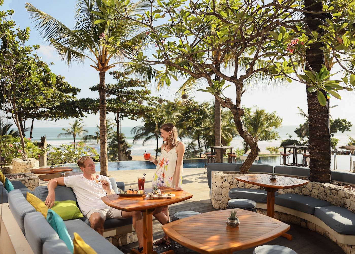 Couple having drinks on an alfresco terrace with cabanas, trees, and an infinity pool at S.K.A.I. Beach Club at Padma Resort Legian in Bali, Indonesia