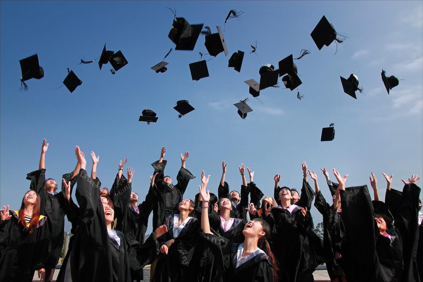 students throwing graduate hats in air