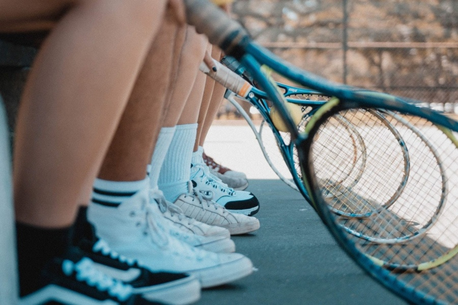 a line of rackets and legs